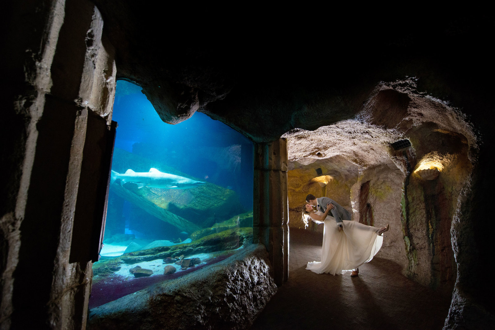 Groom dipping bride in front of sharks at Atlantis Banquet and Events