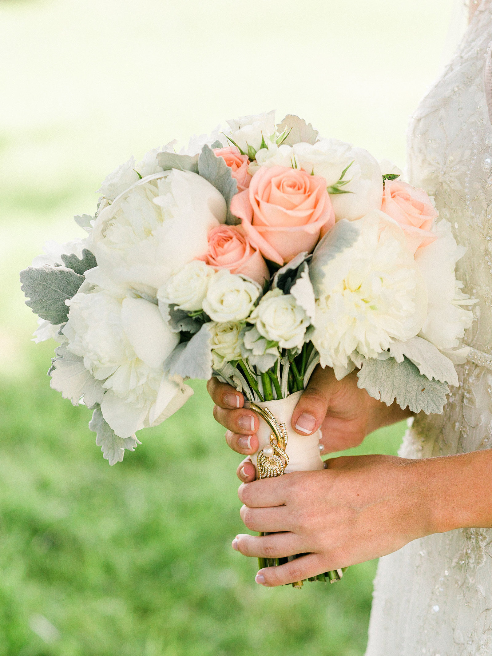 Close up of the bridal bouquet that has an heirloom broach pinned to it