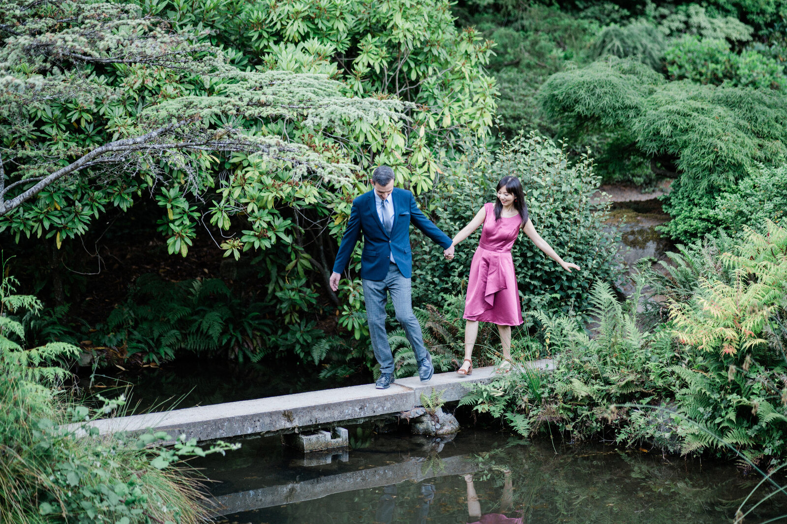 Husband and wife walk across pond at Kubota Garden, romantic place for engagement pictures in Seattle