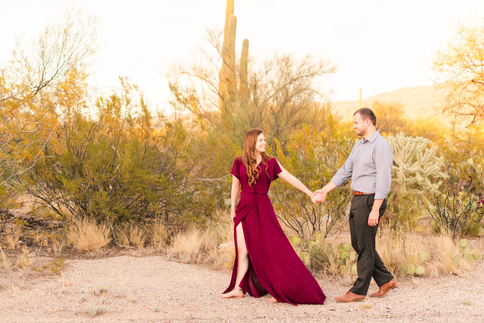 engaged couple walking in Saguaro National Park Tucson desert