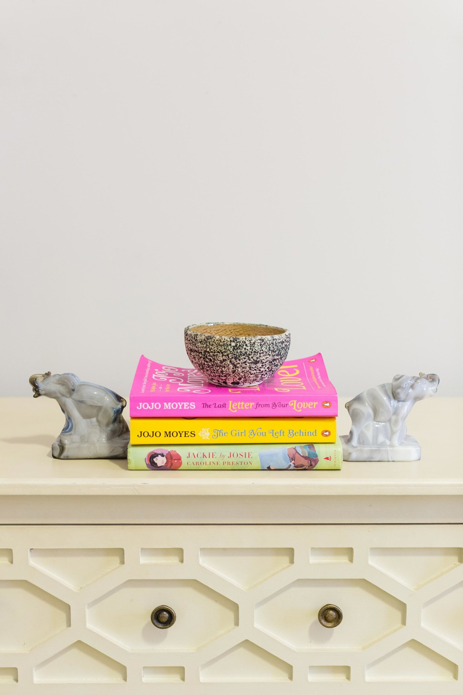 Books, ceramic dish, and bookends on a dresser.