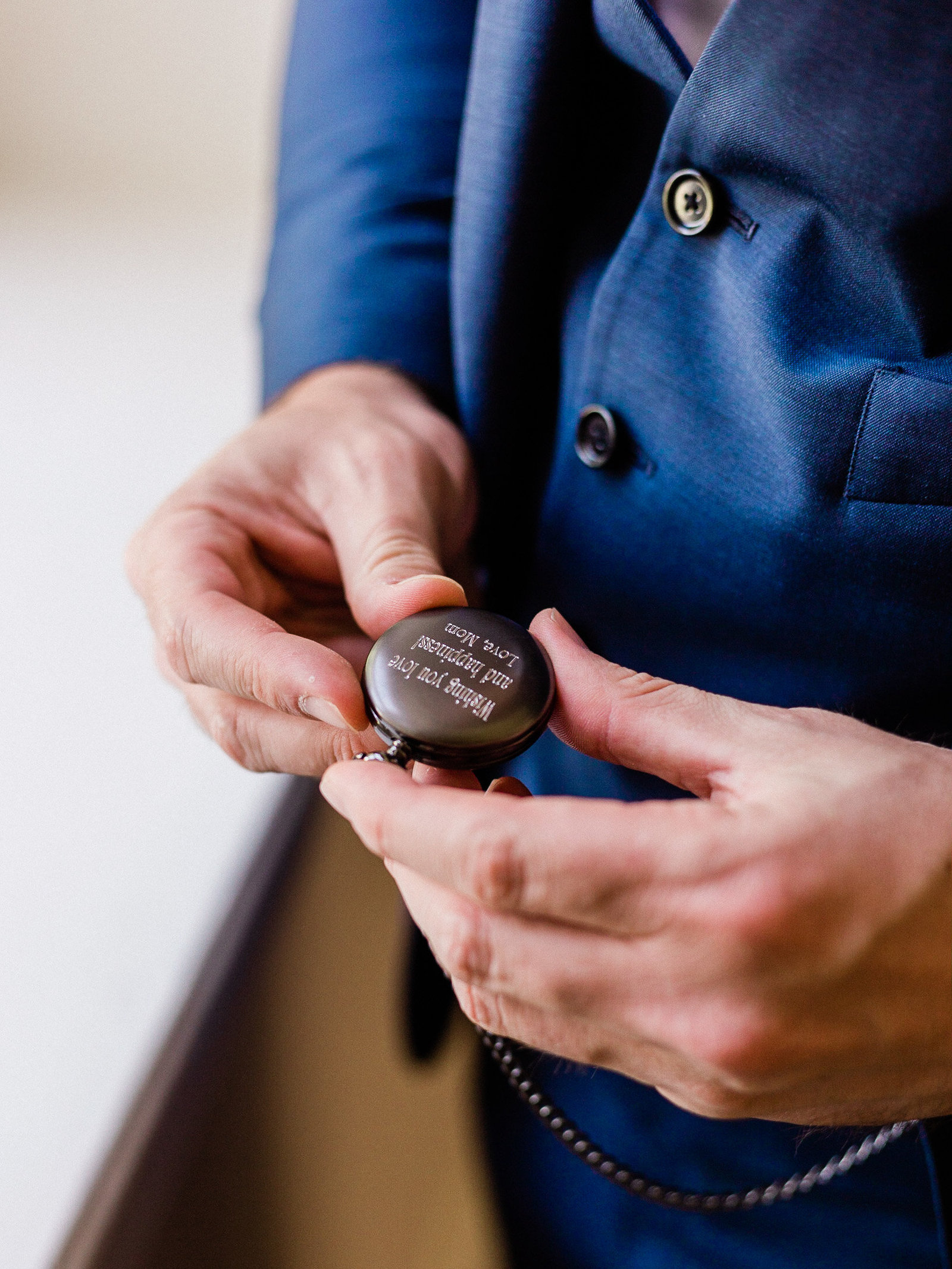 Groom holds custom engraved pocket watch on his wedding day