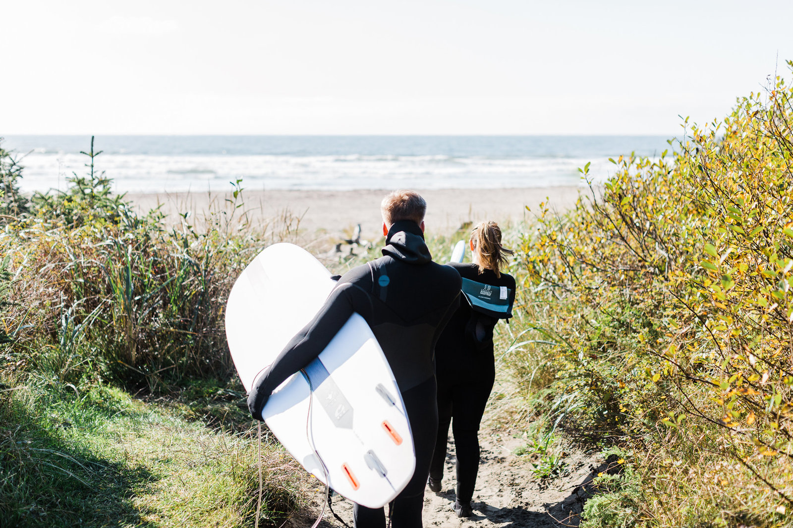 a couple heads out to take a surf together during their adventure engagement session on the washington coast with adventure elopement phototgrapher amy galbraith