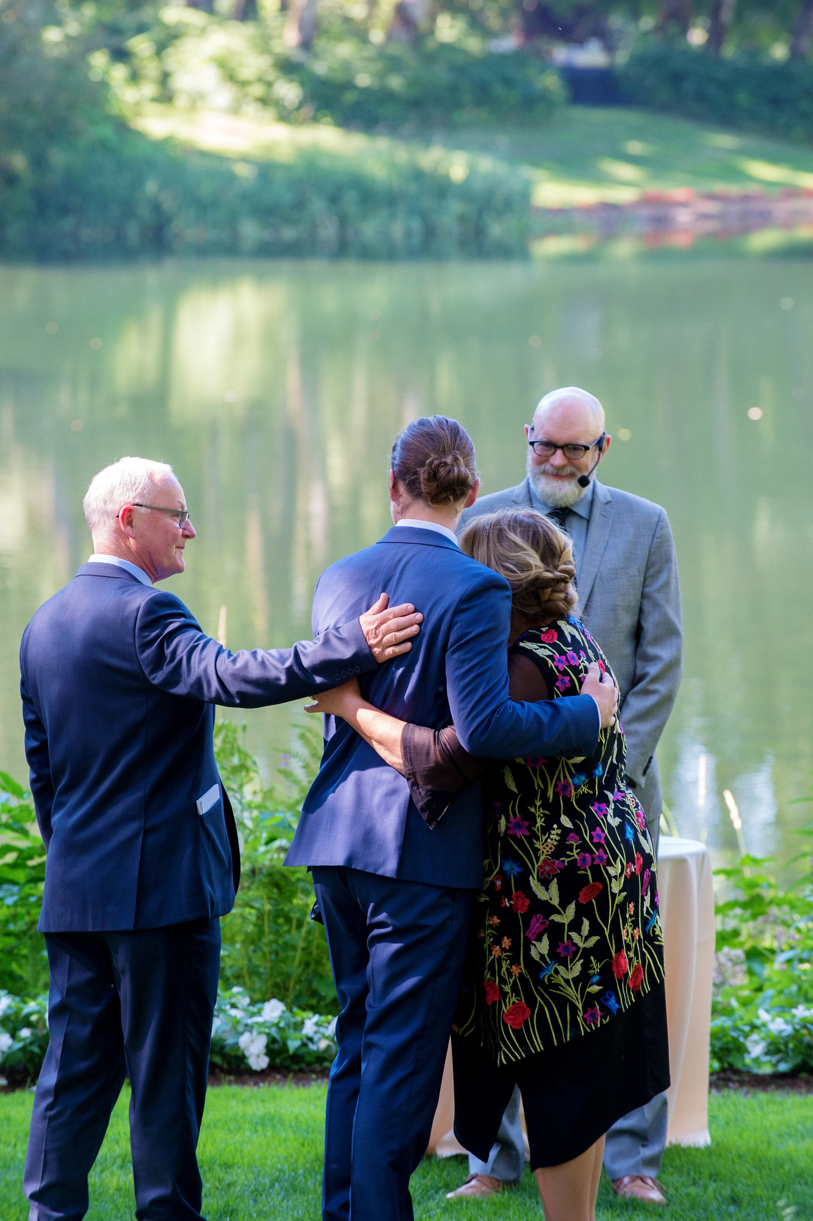 mom and dad hug the groom at the front of the wedding ceremony