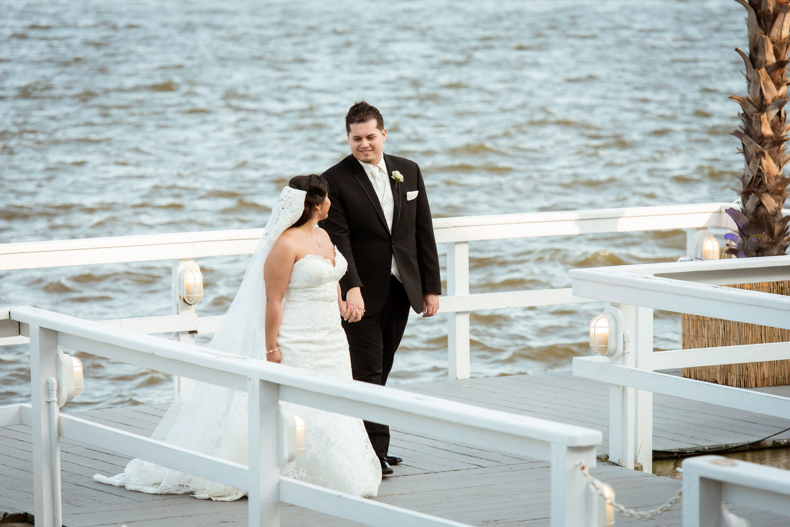 Bride and groom walking on dock at Chateau La Mer