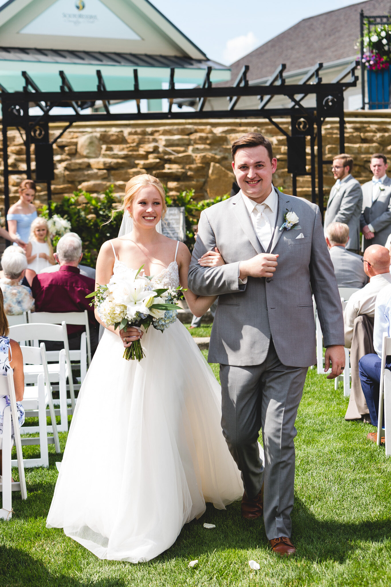 bride and groom recessional smiling with flowers ohio wedding