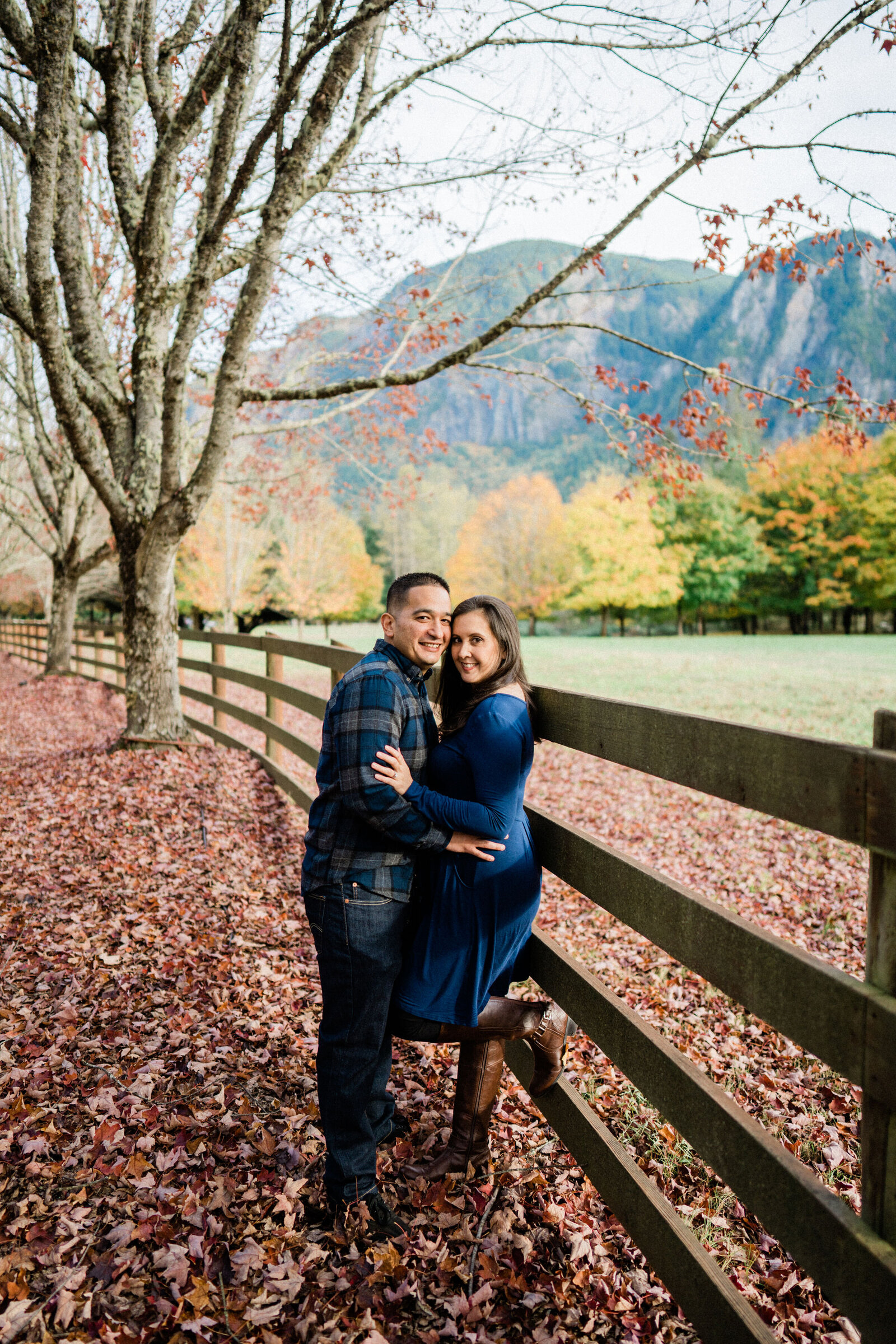 Couple hugs and kisses at Rockwood Farm, best spot for engagement photos with fall color in Seattle