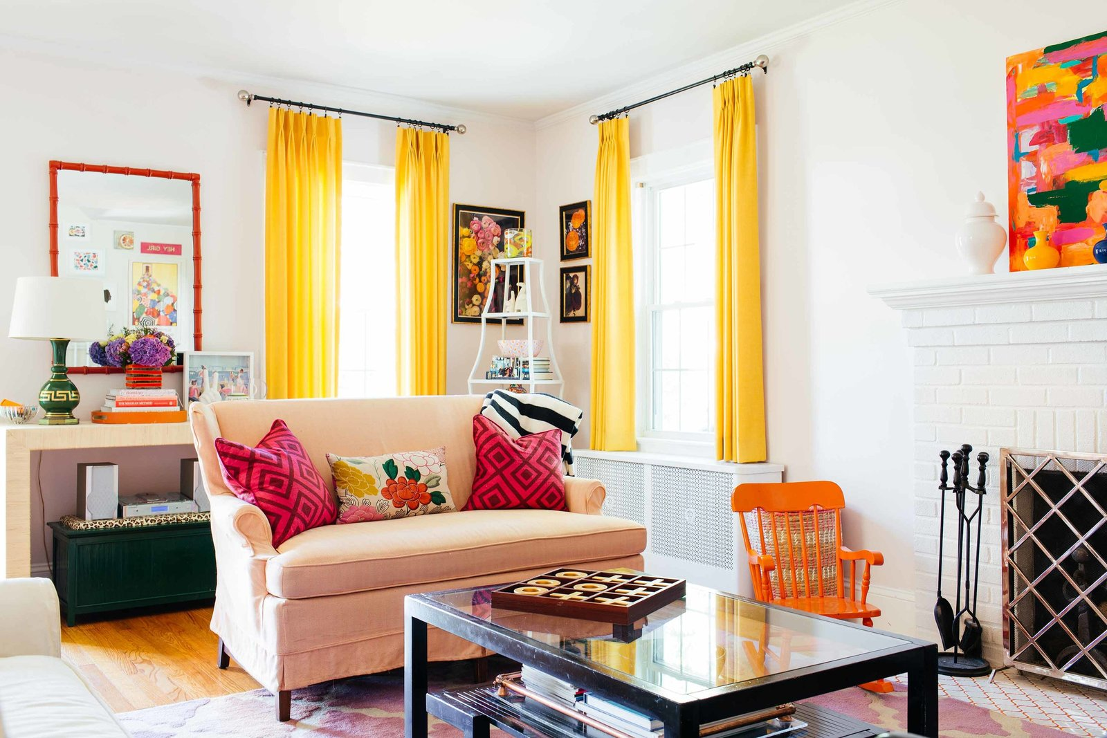 A peach love seat in a colorful living room.