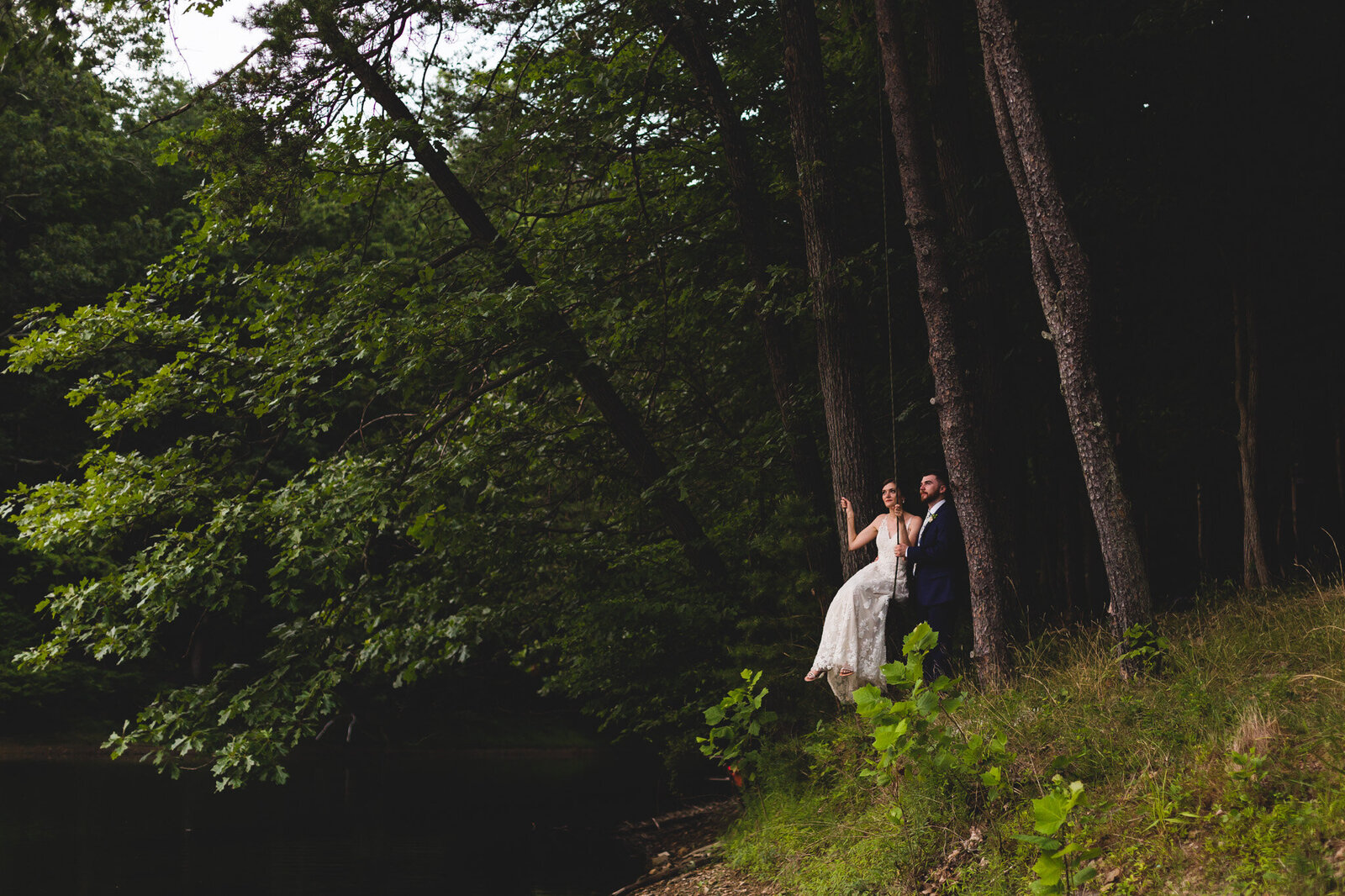 bride and groom swing by a lake on wedding day ohio