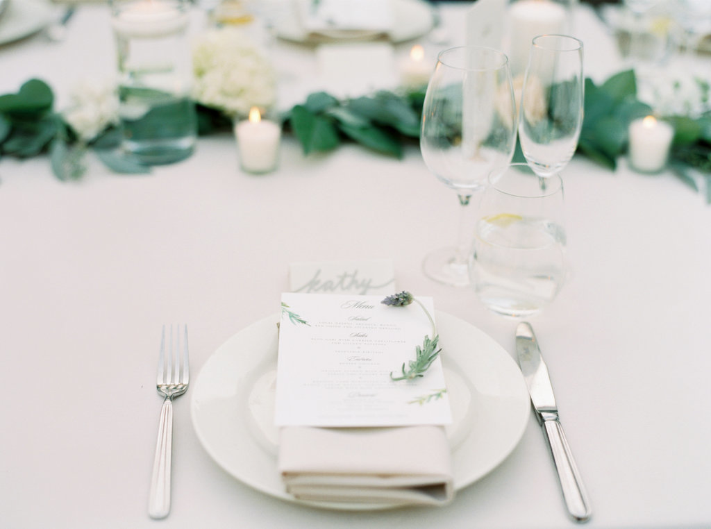 Classic wedding reception table setting with white plates, menu card and white floral centerpieces at Butterfly Lane Estate in Montecito