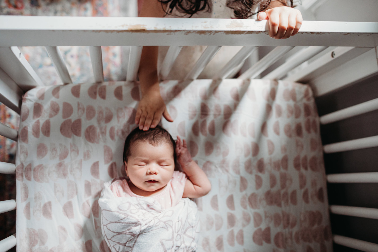 sibling reaches through crib bars to touch babys head during natick newborn session