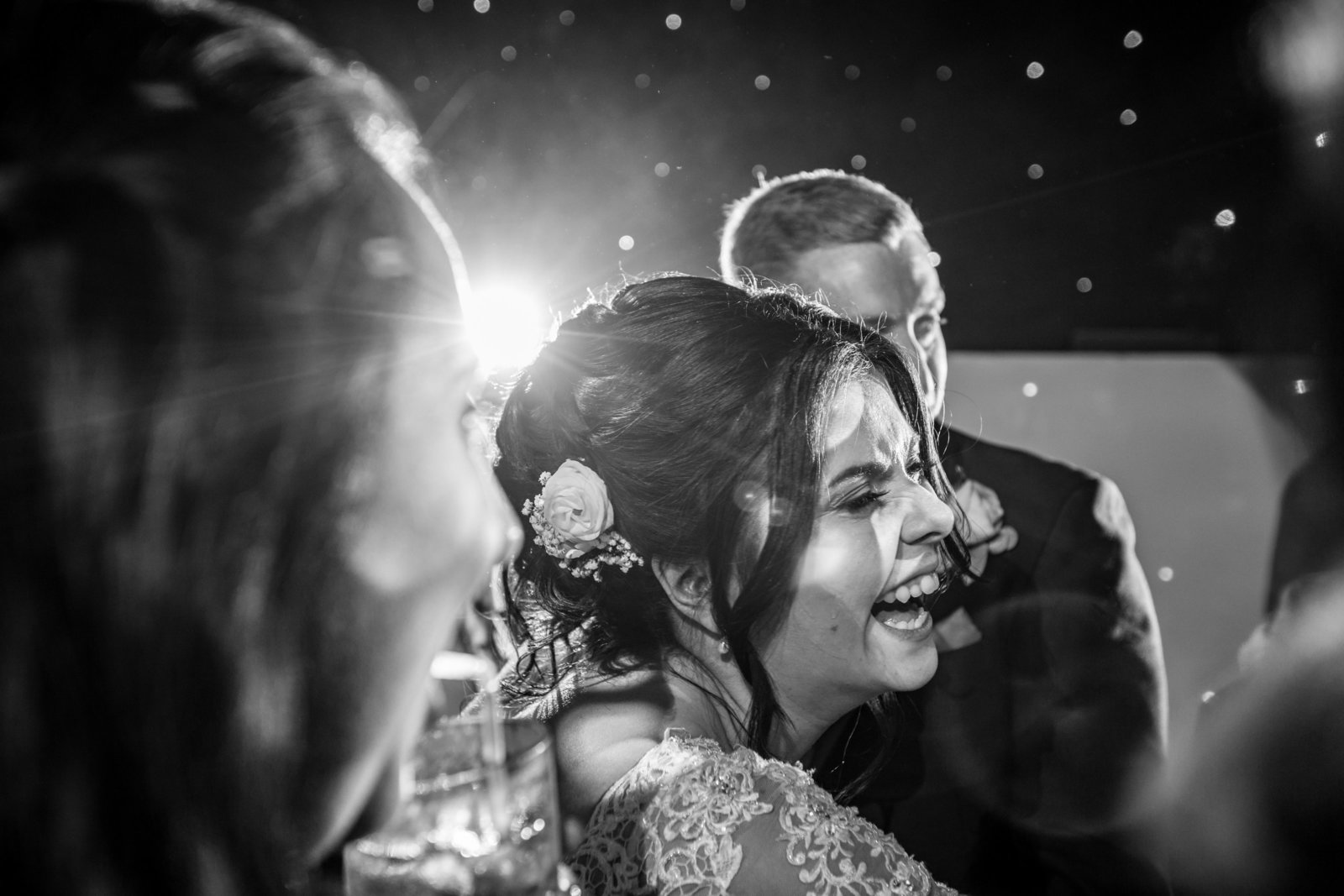 A bride laughs and cries whilst there is lighting behind her on a dance floor in Norfolk.