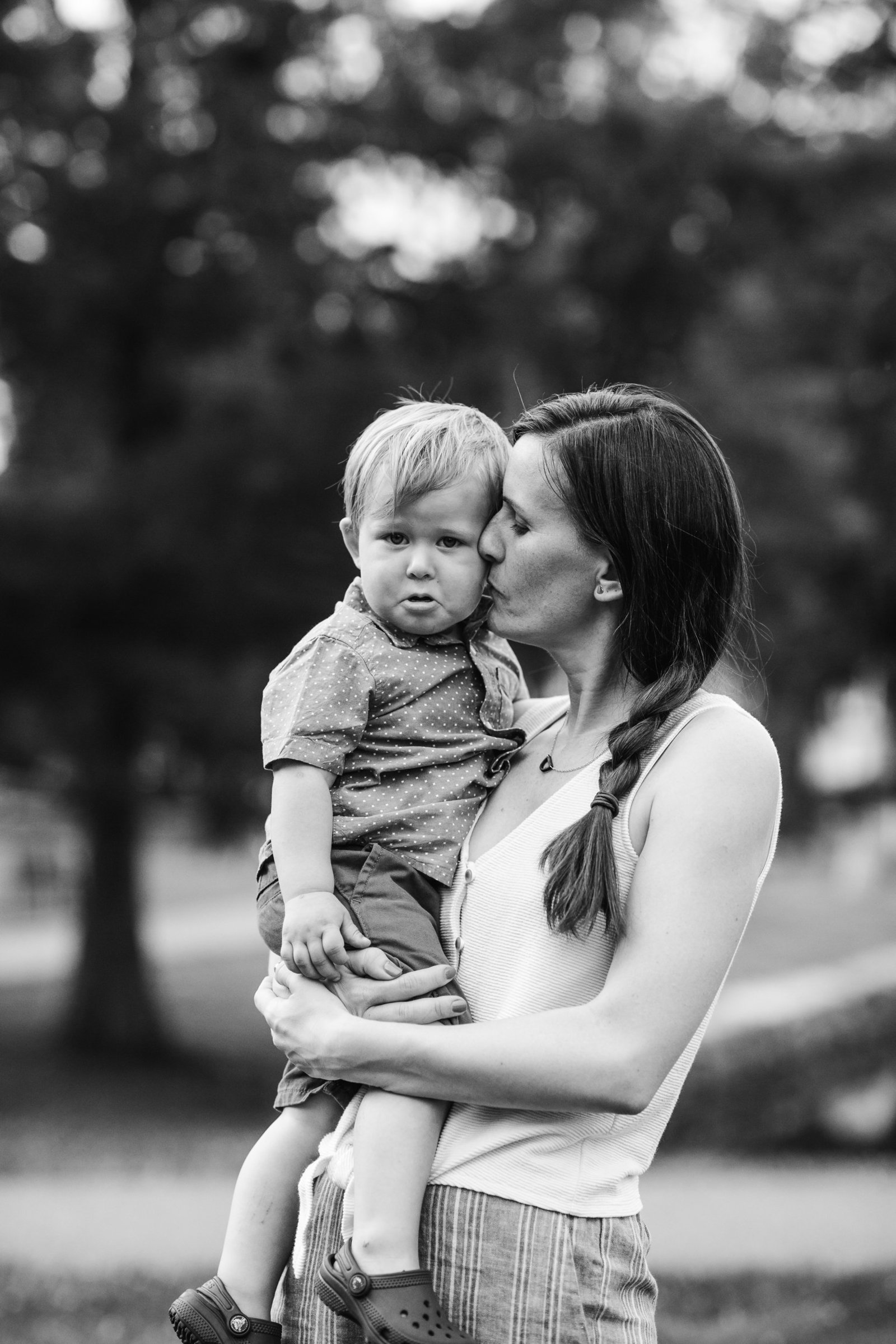 black and white portrait of mother holding toddler son who is crying in boston ma