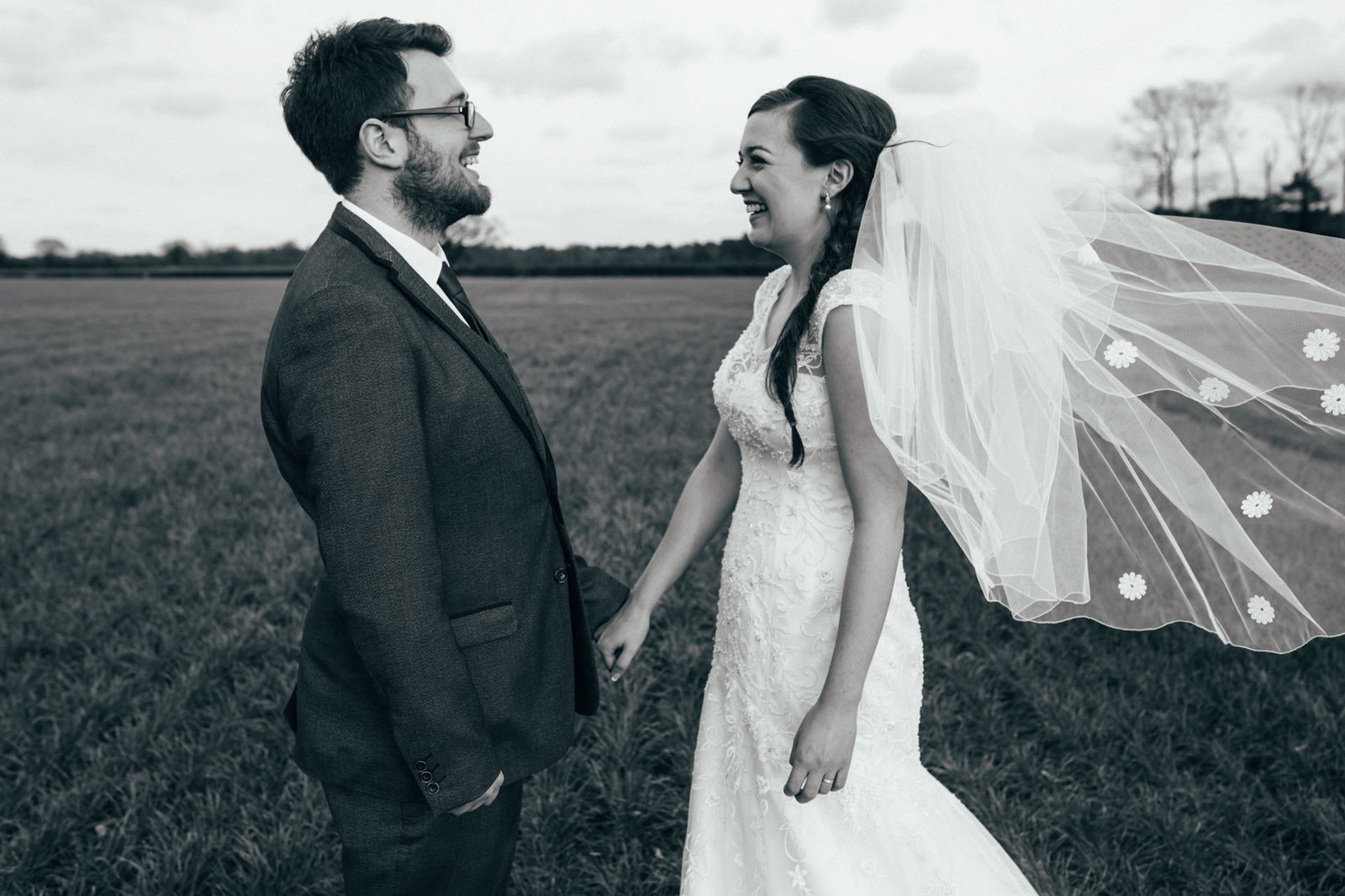 Laughing black and white photograph of bride and groom holding hands in a field at their Wood Farm Barn in Suffolk Wedding