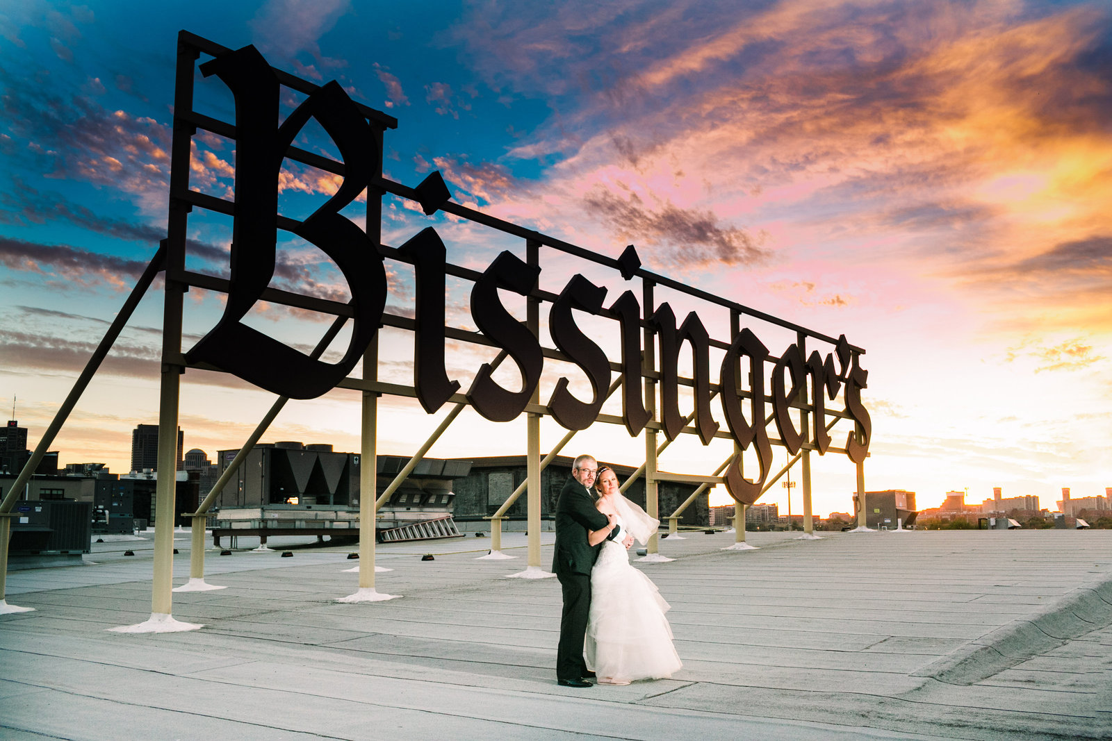 Bride and Groom, Sarah and Chris, stand on the rooftop of Bissinger's Caramel Room with their sign in the background and a blue and orange sunset.