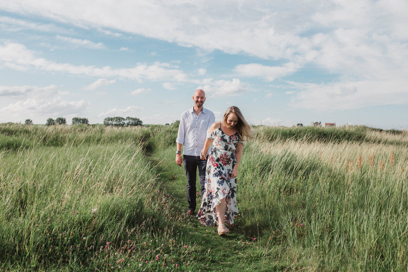 Natural photograph of relaxed couple laughing and walking  outside under a tree in the Norfolk countryside