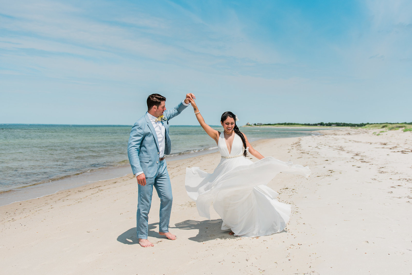 A bride and groom dancing on Falmouth beach for their intimate Cape Cod wedding ceremony