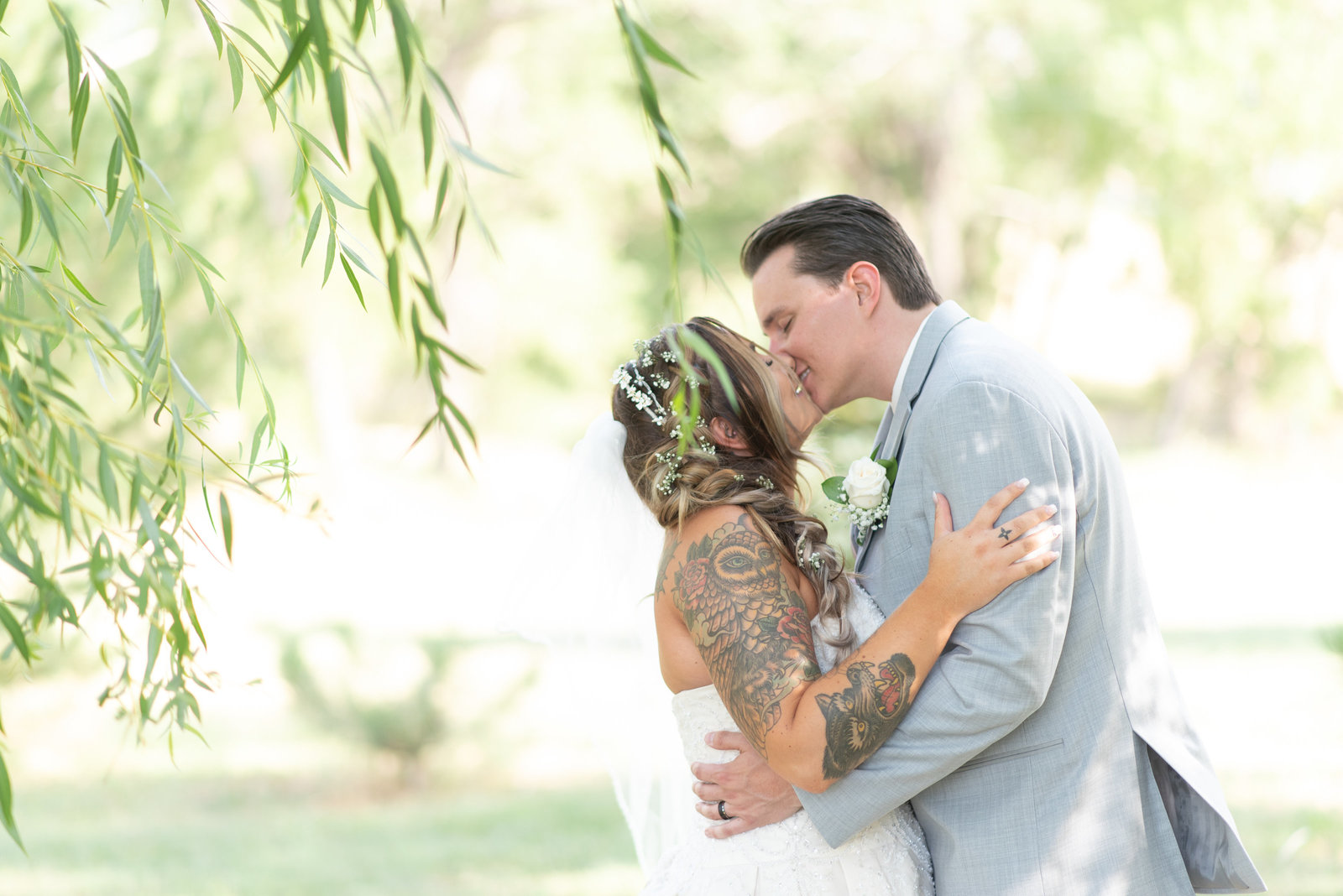 Bride and groom kissing under a willow tree Byers, Colorado