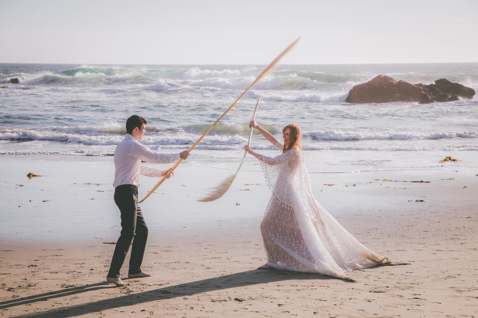 A bride and groom play fight each other using pampas grass on a beach.