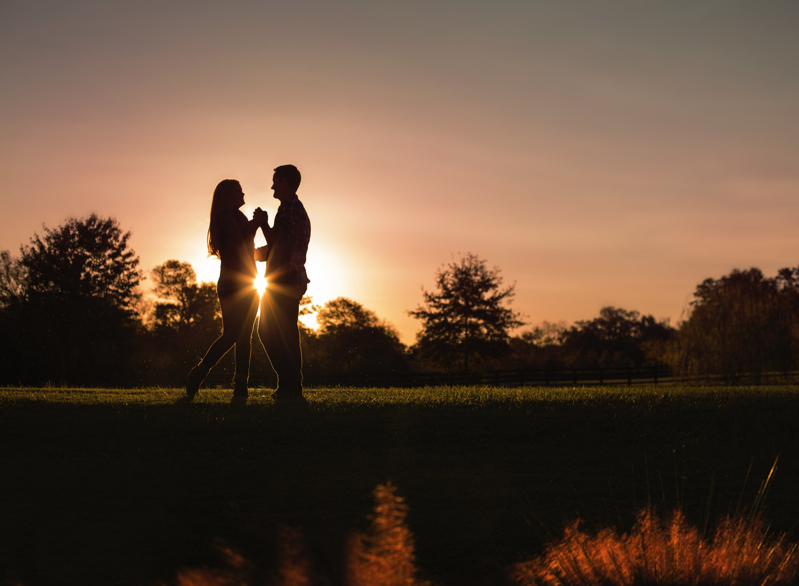charlotte engagement photographer jamie lucido at Morning Glory Farm at sunset creates a beautiful silhouette of engaged couple dancing