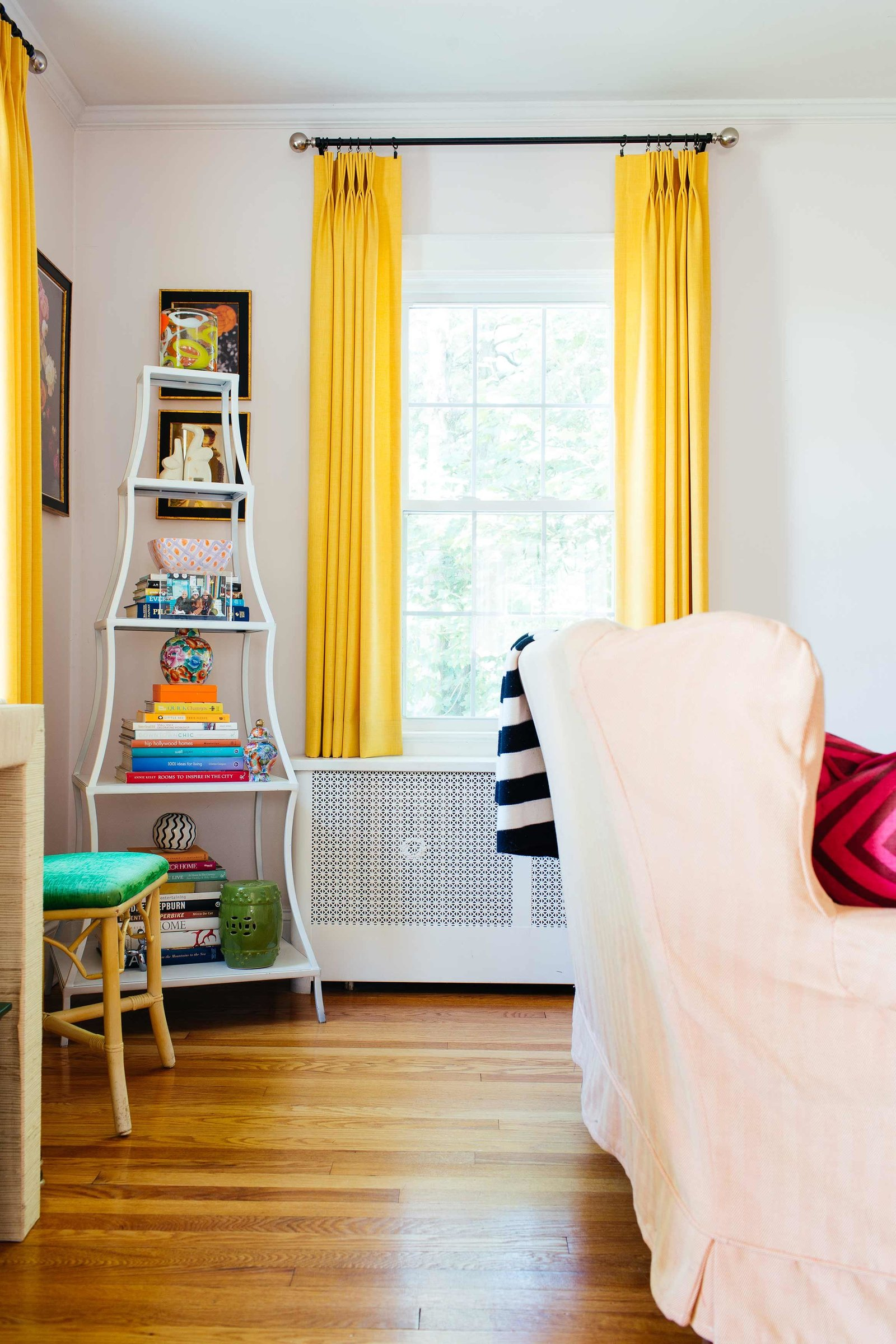 Yellow drapes on white walls and white bookcase.