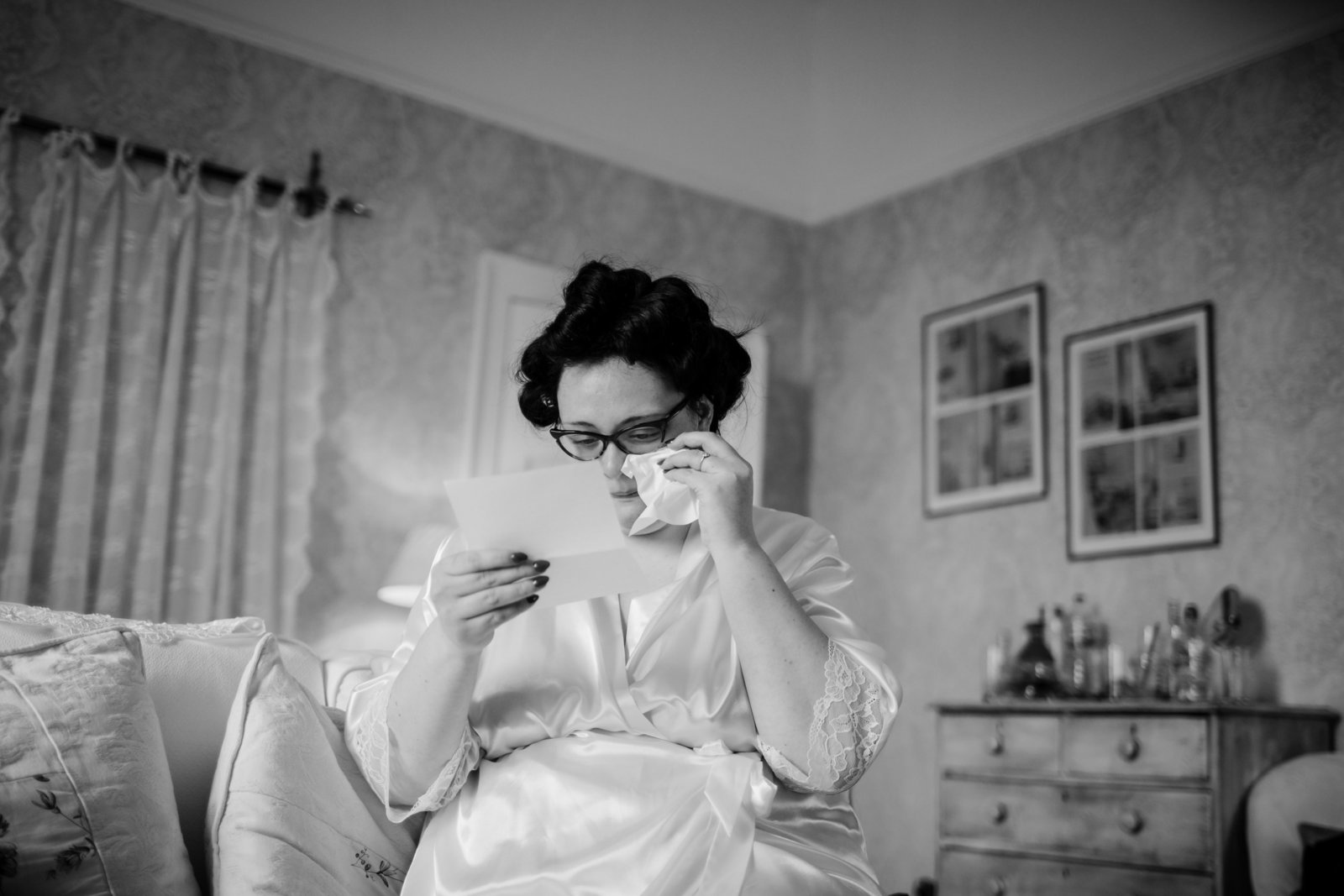 A bride with happy tears before her wedding while reading a card from her future husband at a Norfolk wedding venue.