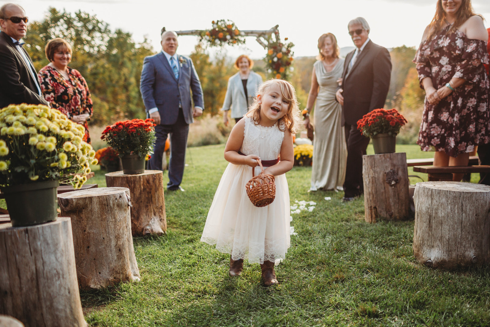 flower girl smiles and walks down outdoor aisle