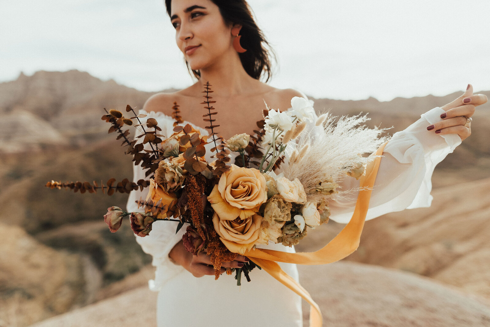 Bride holding her bouquet standing in the Badlands