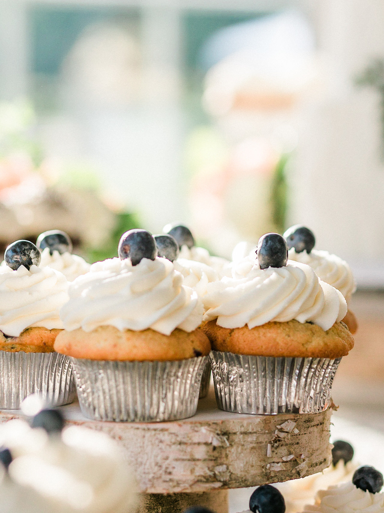 Country style cupcakes with blueberries on a birch wood stand