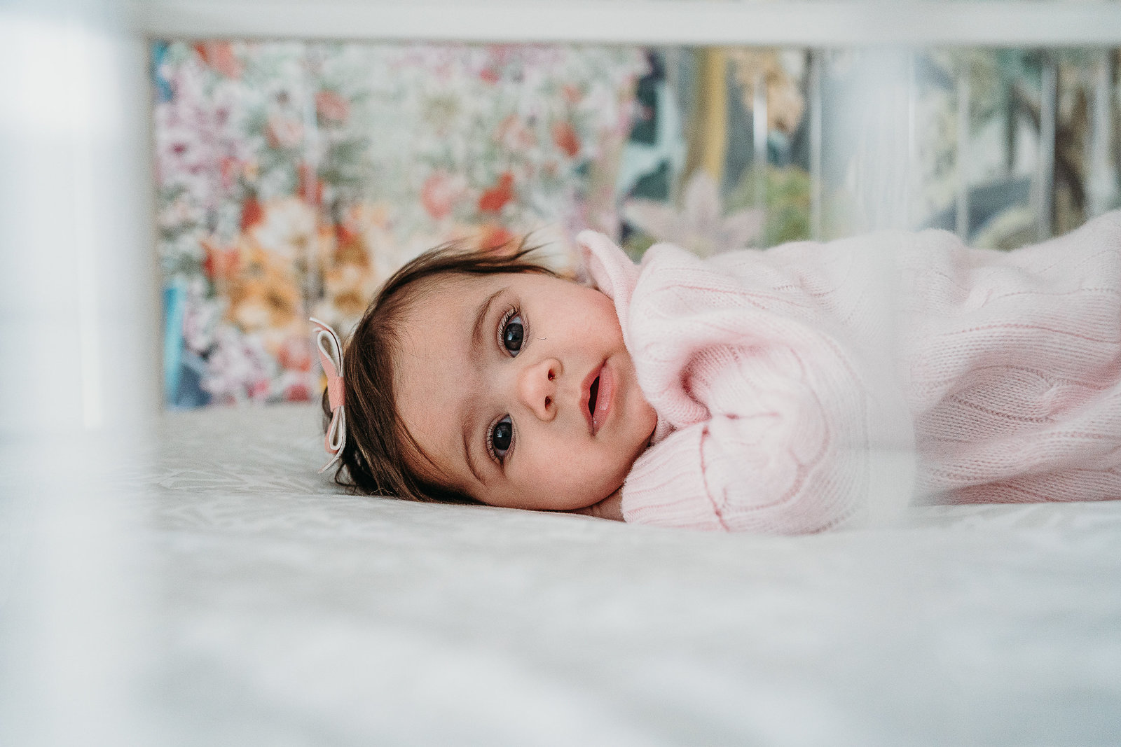 baby girl in pink looks out of crib bars during photos in boston