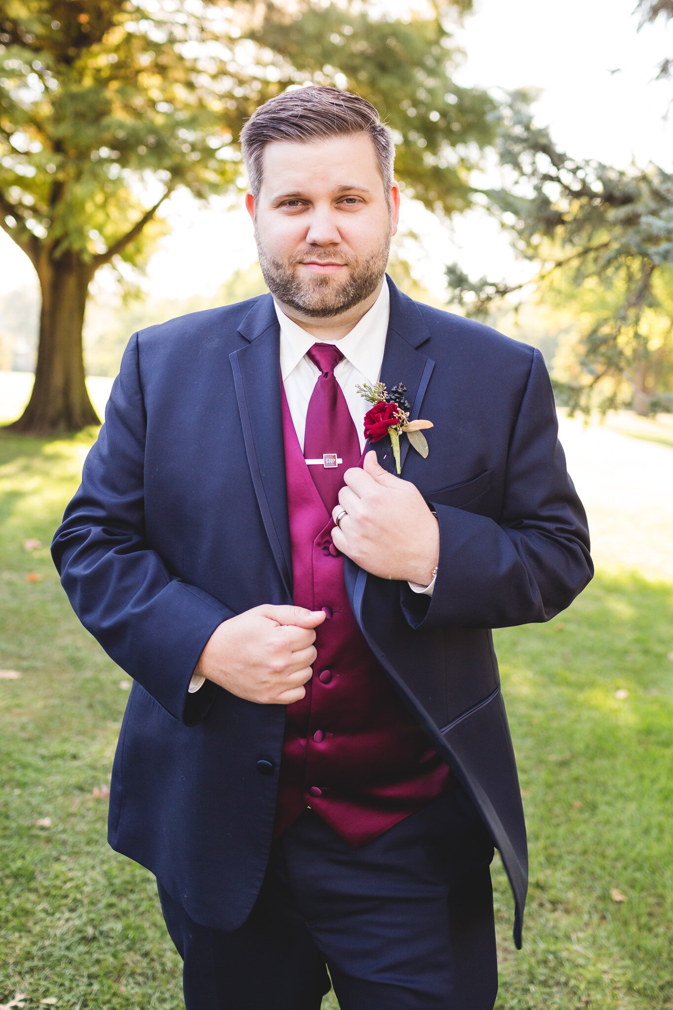 dapper groom posing for wedding day photographer in ohio