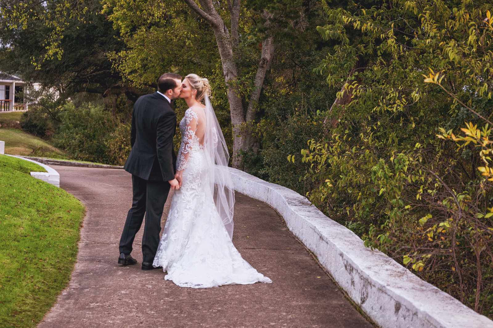 bride and groom kiss on pathway