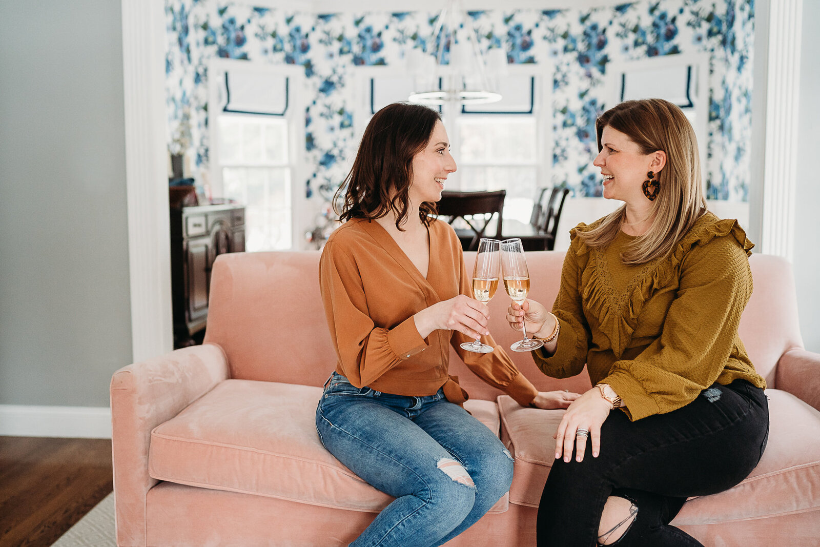 female entrepreneurs toast champagne while sitting on a pink couch