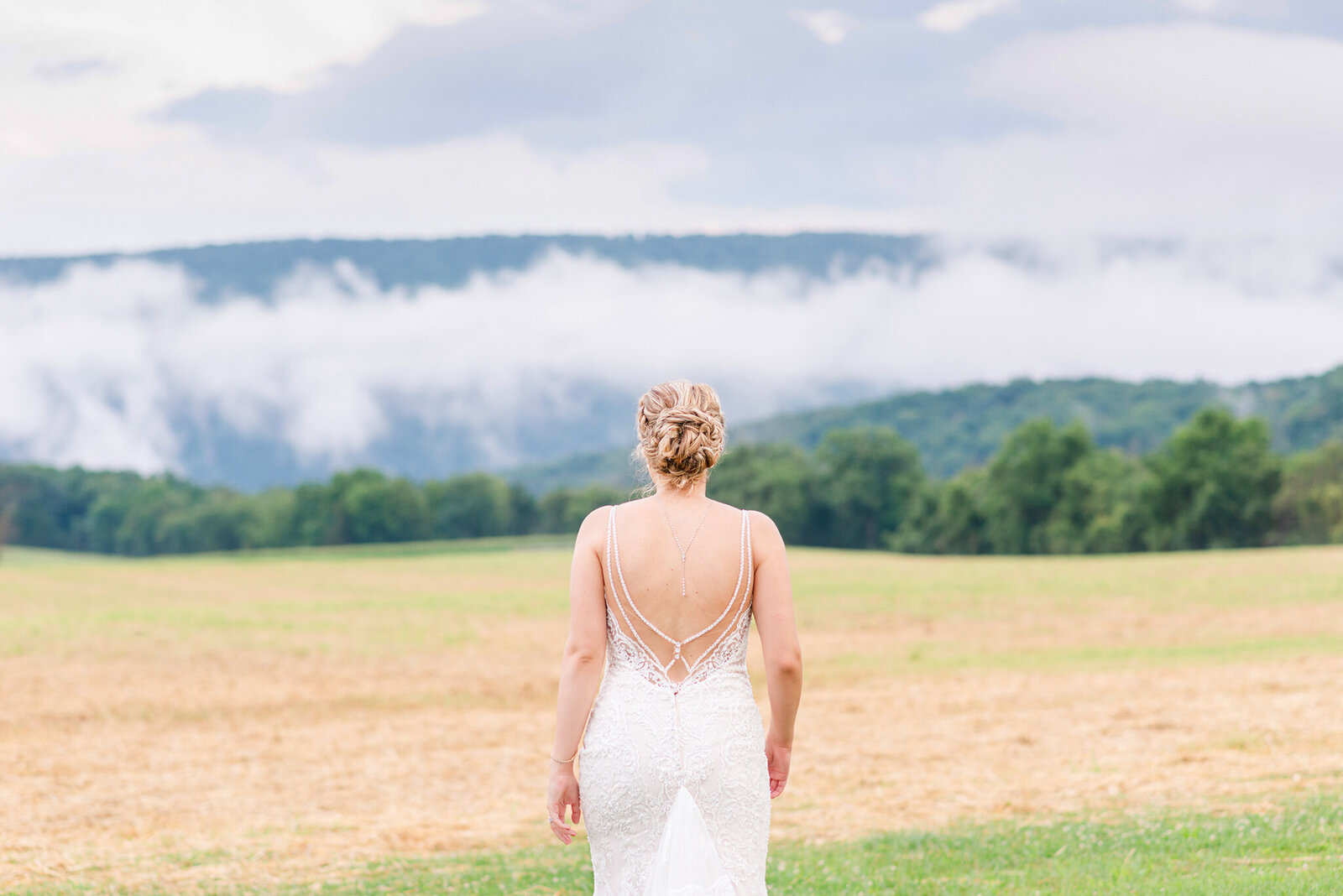Bride facing fog-covered mountains