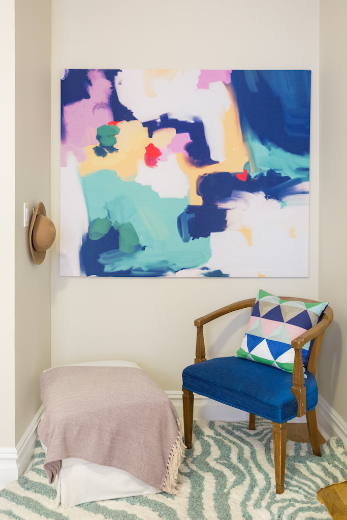 A blue chair and ottoman and bright abstract painting.