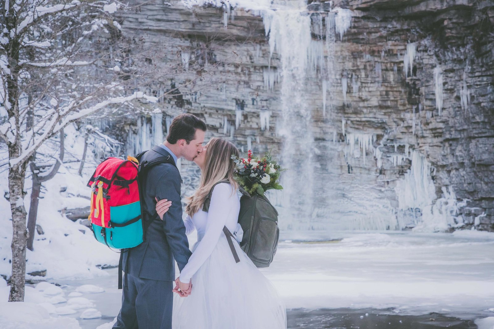 Groom and bride wear backpacks and kiss with New York waterfall in background.