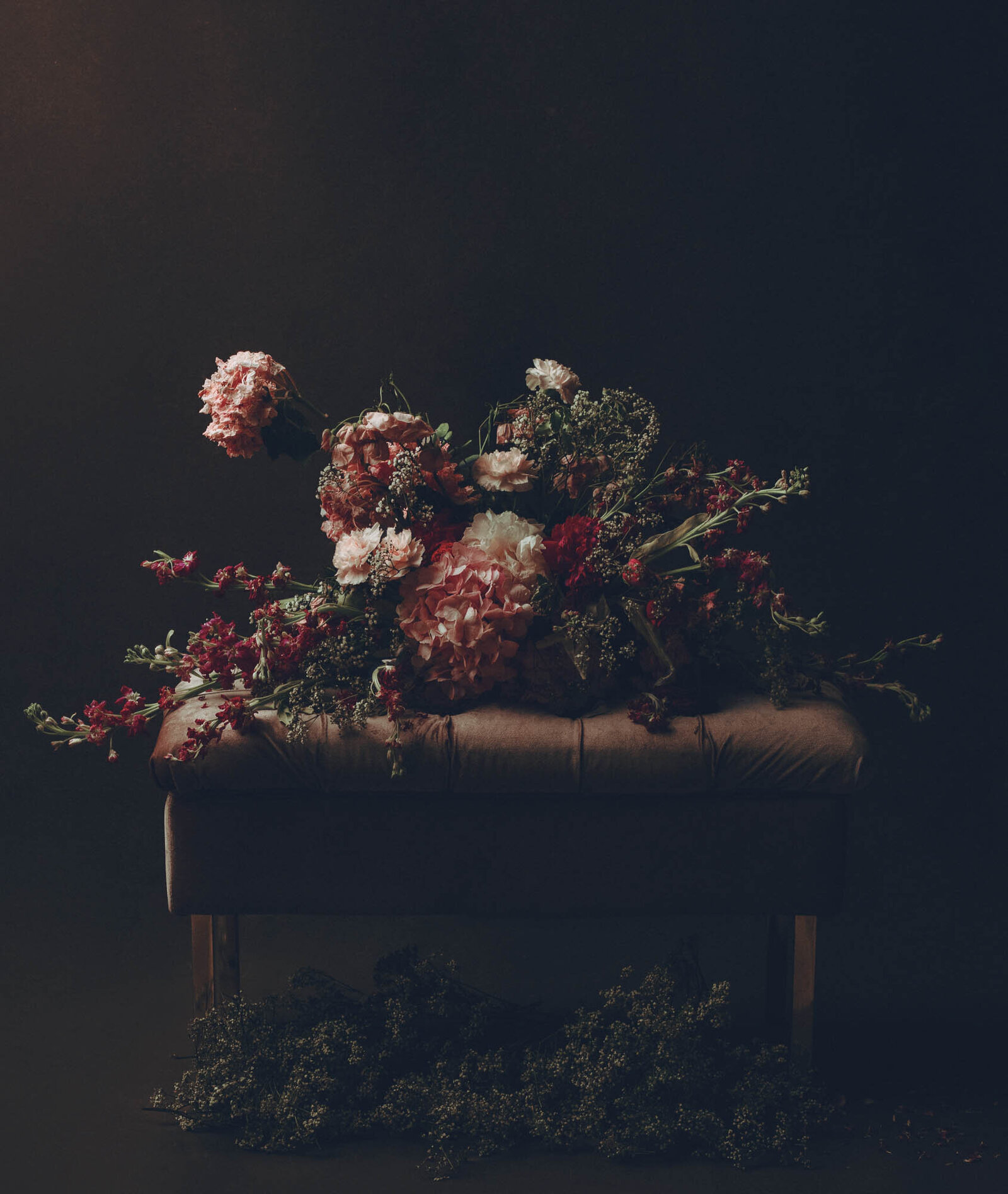 Artful picture of a bouquet  of flowers on a leather sofa.