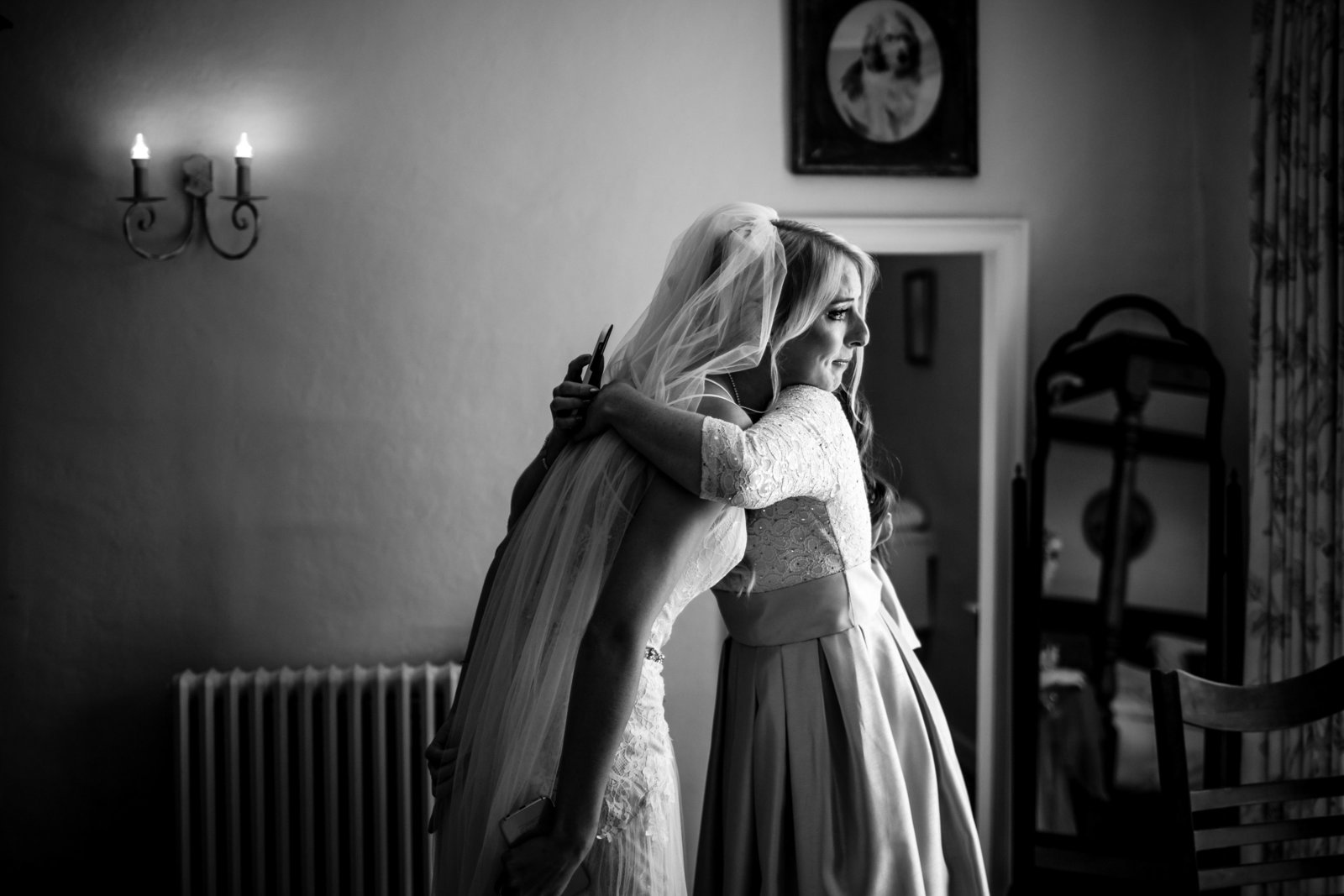 A bridesmaid gives an emotional bride a hug before the wedding ceremony
