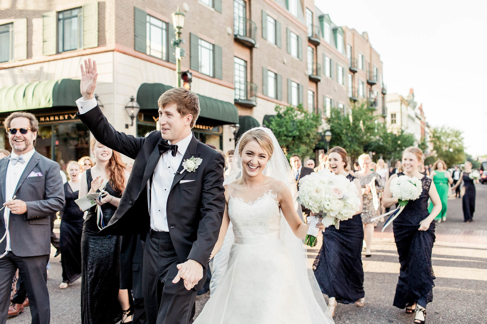 Bride and groom march down King Street with Burke high school marching band, Charleston, South Carolina. Kate Timbers Photography.