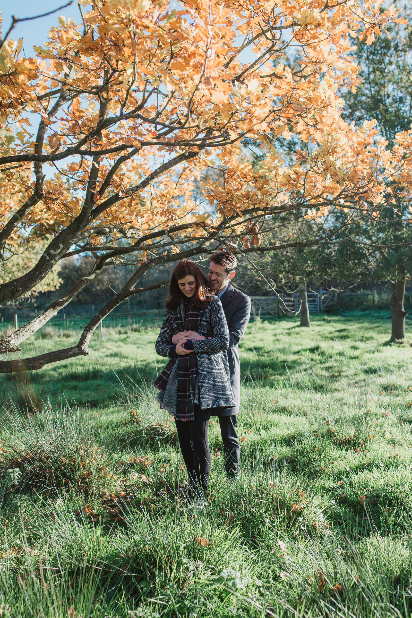 Natural photograph of relaxed couple laughing and cuddling outside under a tree in the Norfolk countryside