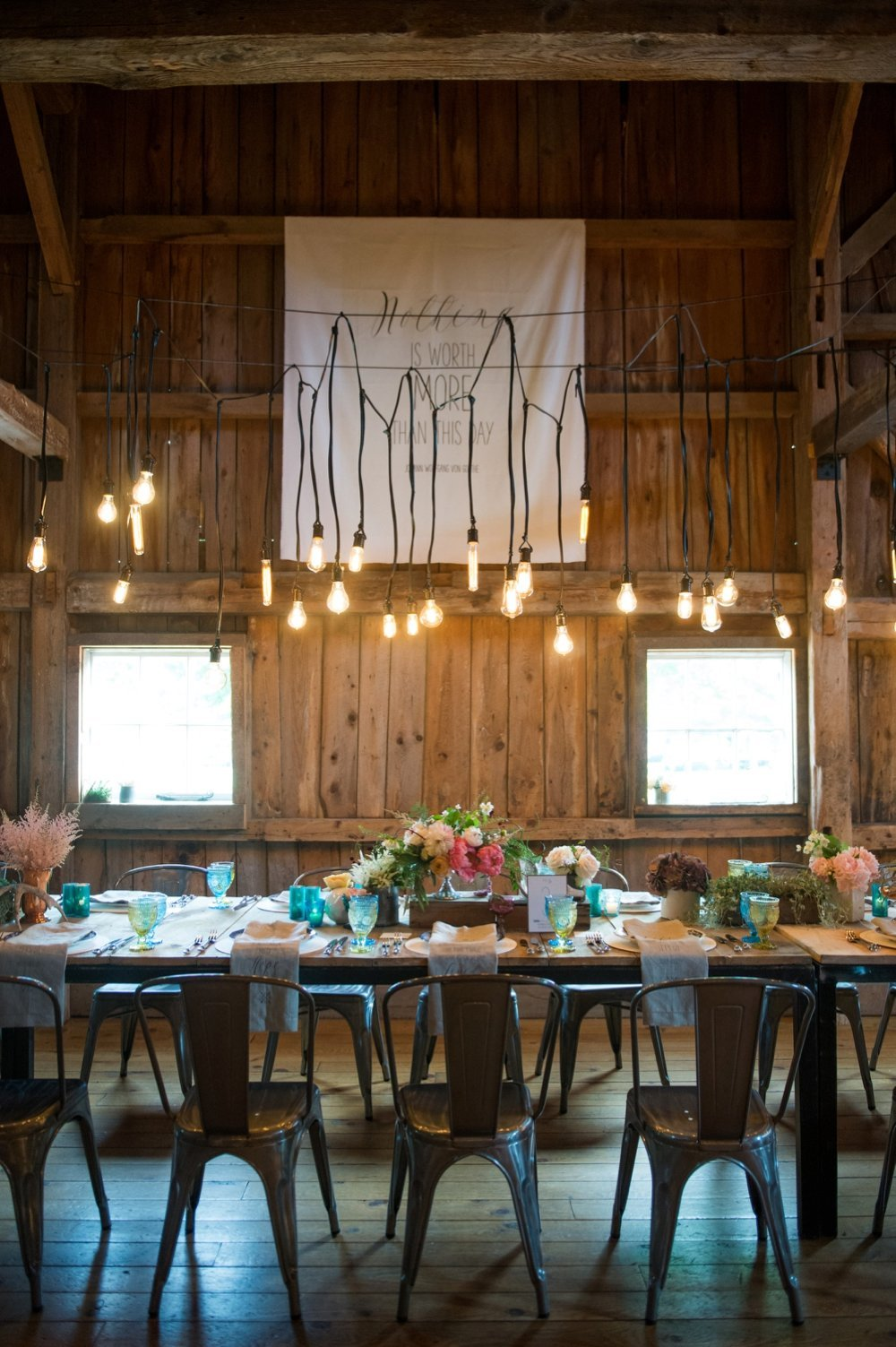 Gorgeous rustic tablescape for barn wedding with Edison Bulb light installation