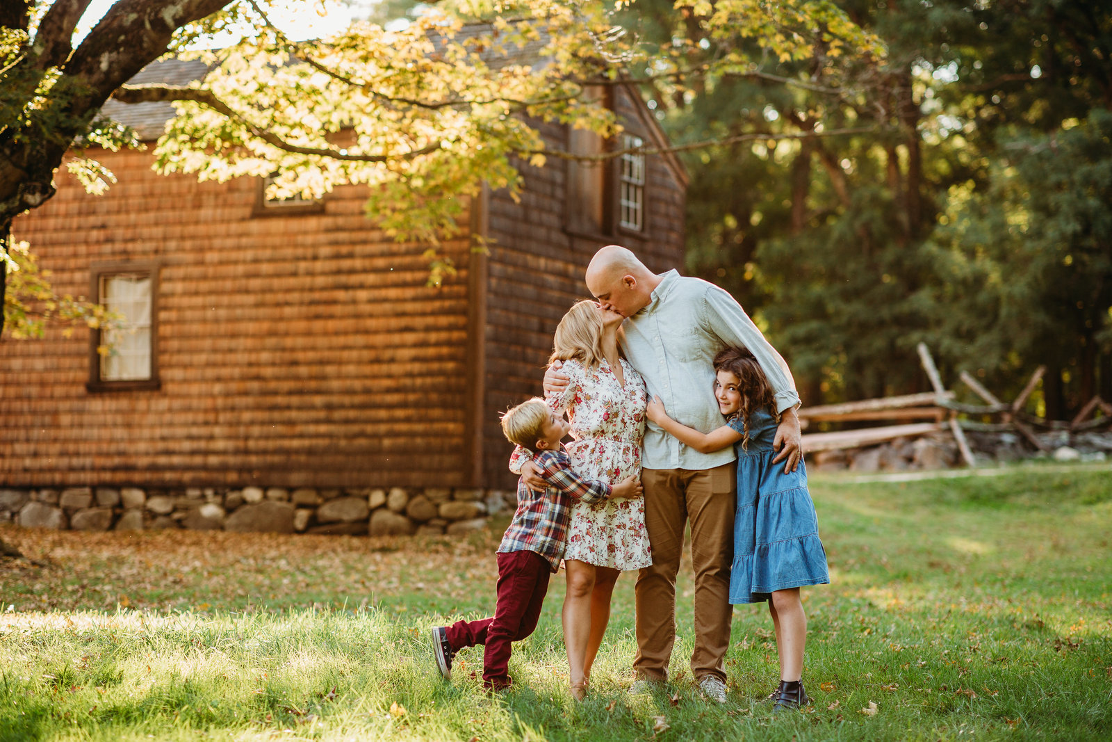 family with two older kids smooches under autumn tree in lincoln massachusetts