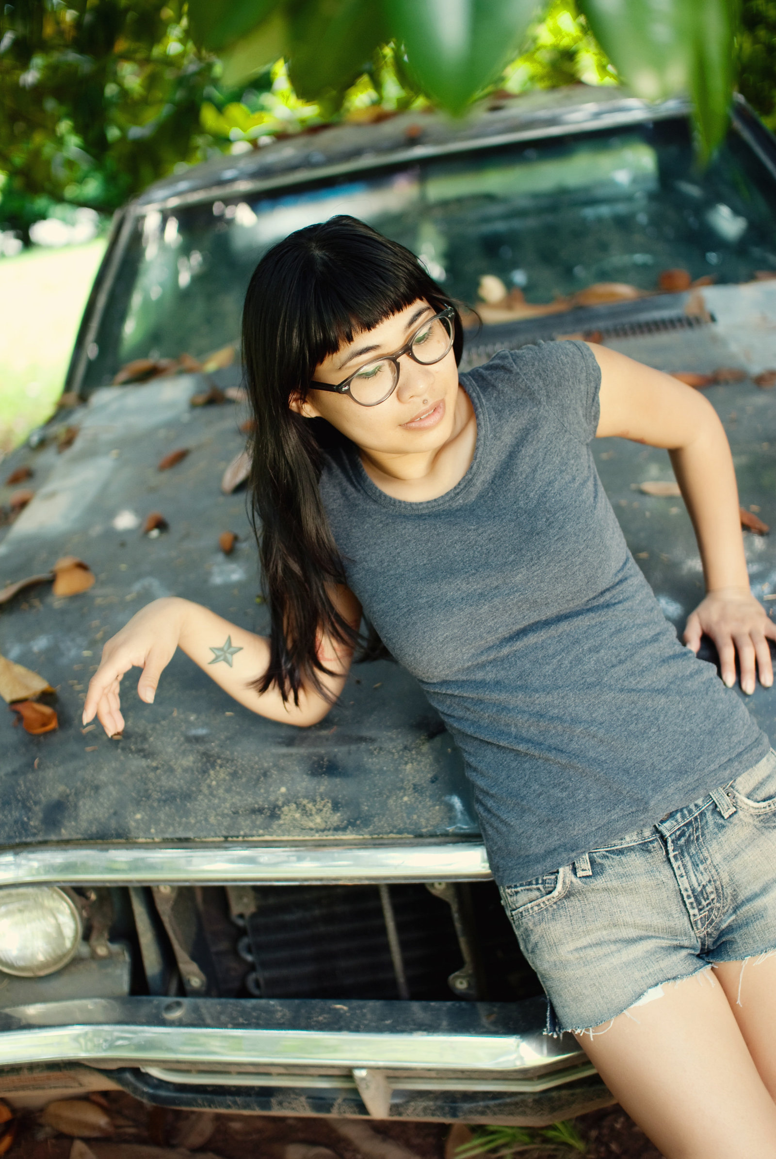 a girl leans against an old vintage car