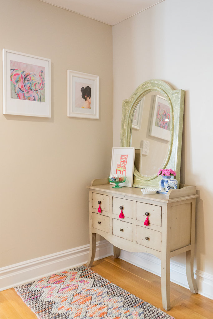 A vintage vanity and mirror with framed art.