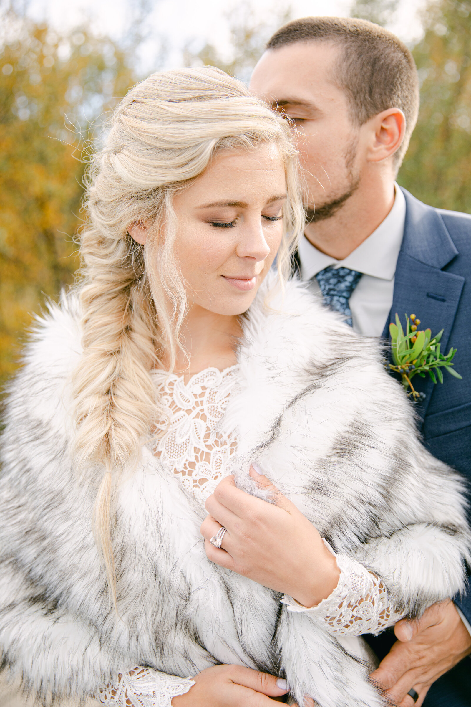 bride looking at the ground holding her fur coat as groom kisses the side of her head