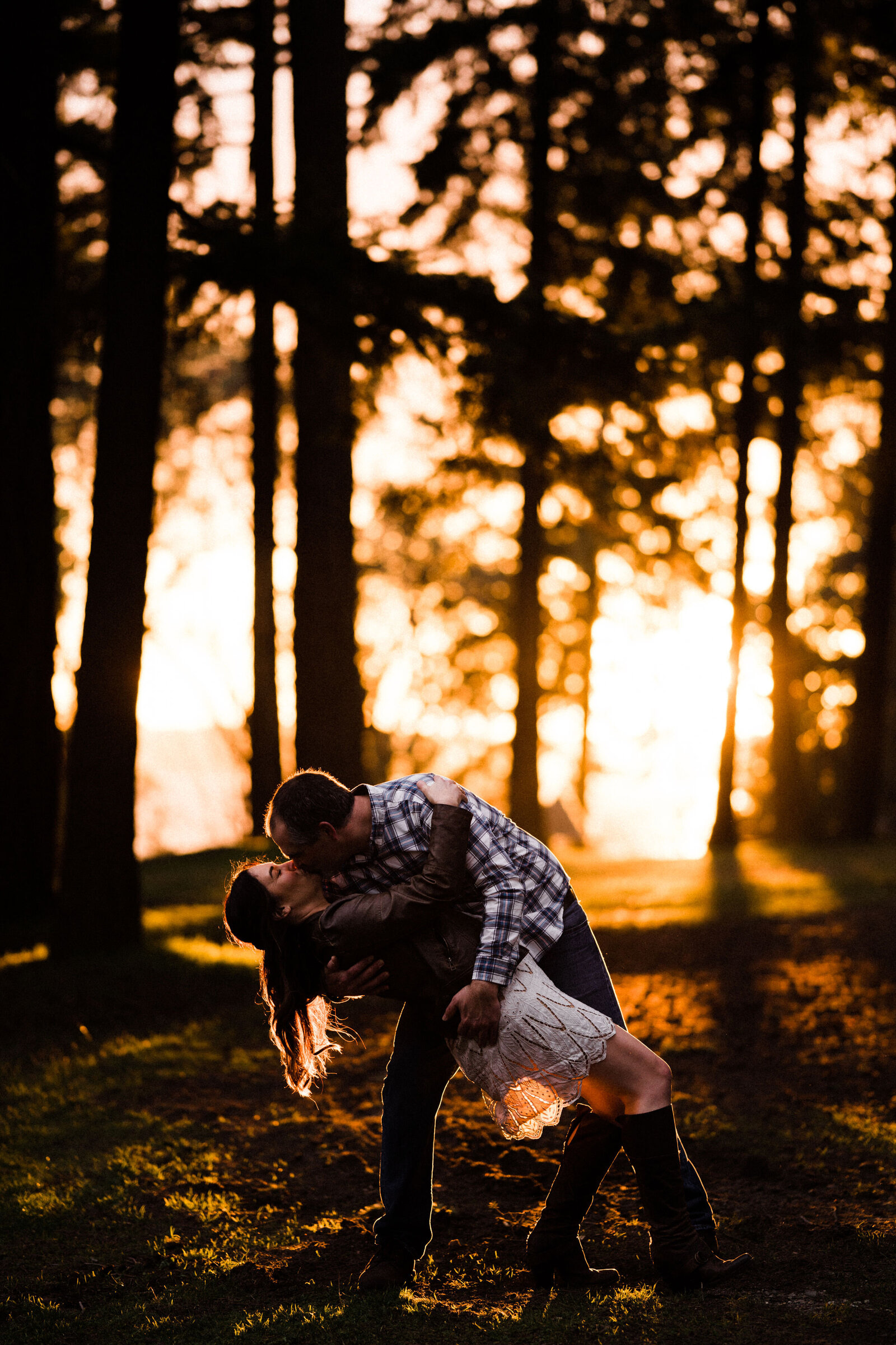 Couples kissing at Lincoln Park in West Seattle. Sunset, meadows, trees, beaches. It's one of the best spots for engagement photos in Seattle.