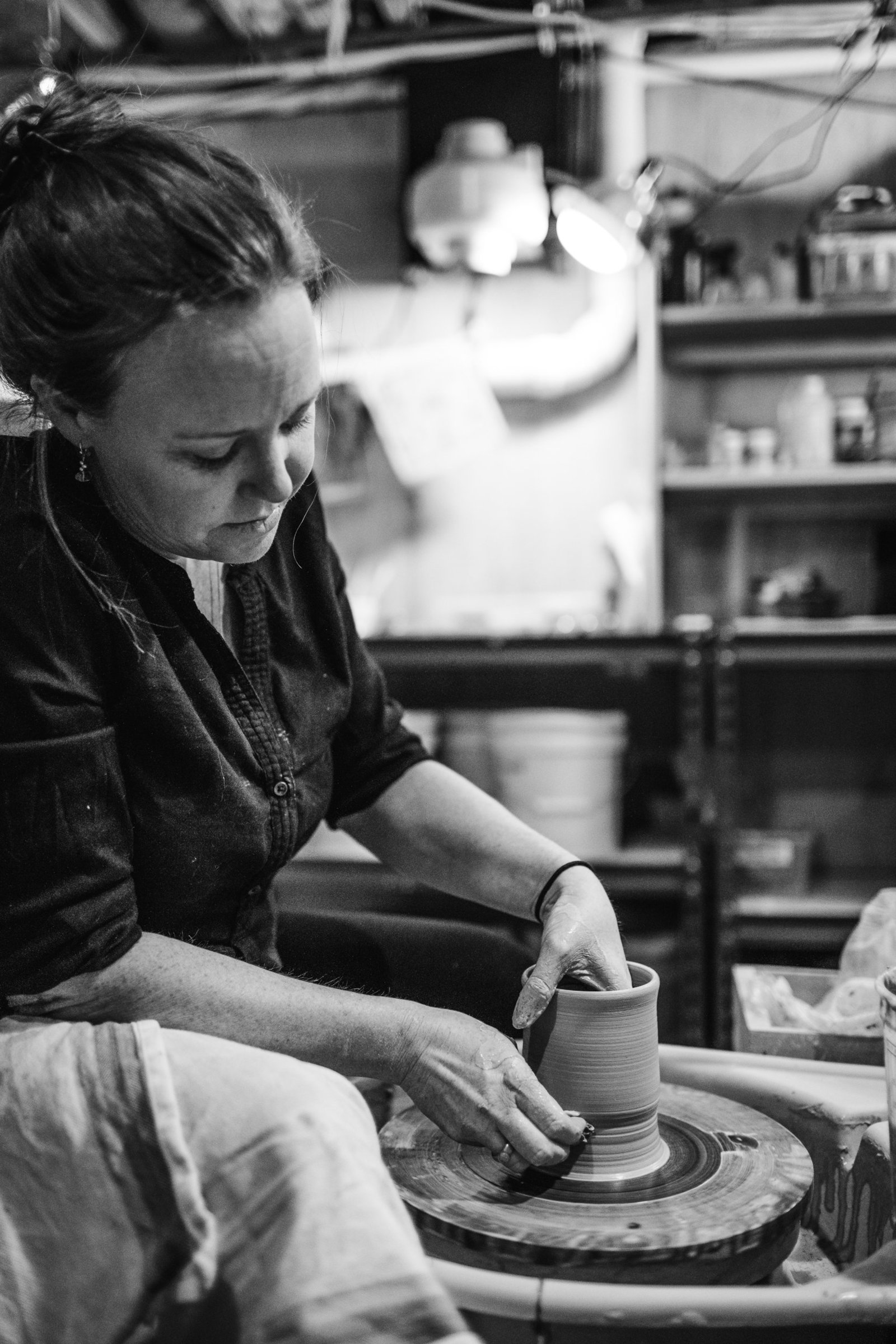 woman shapes clay during pottery photography session