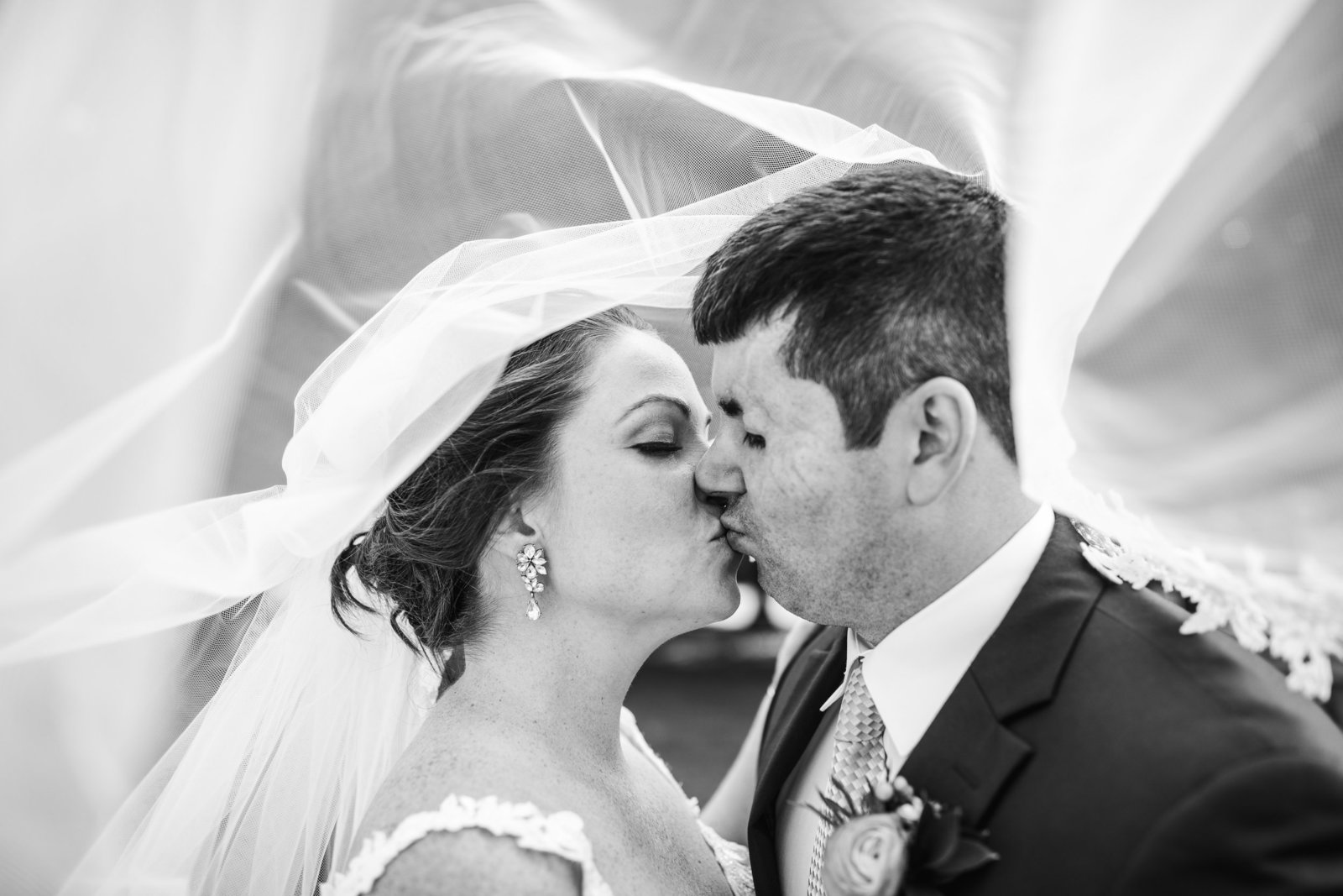 bride and groom kiss under veil for couples portraits in massachusetts