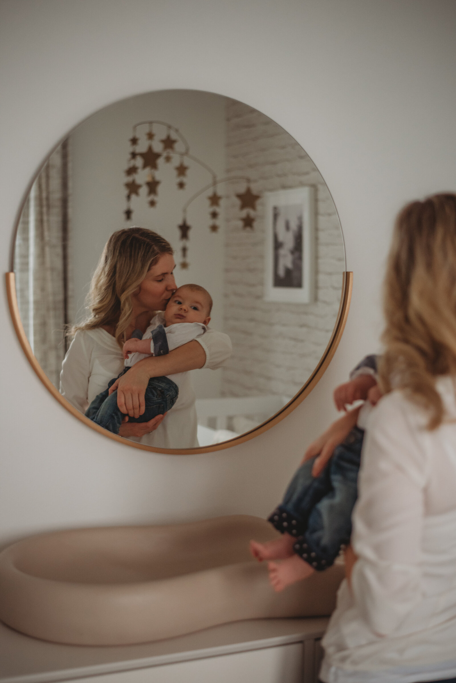 Mother holding her baby son in front of a mirror