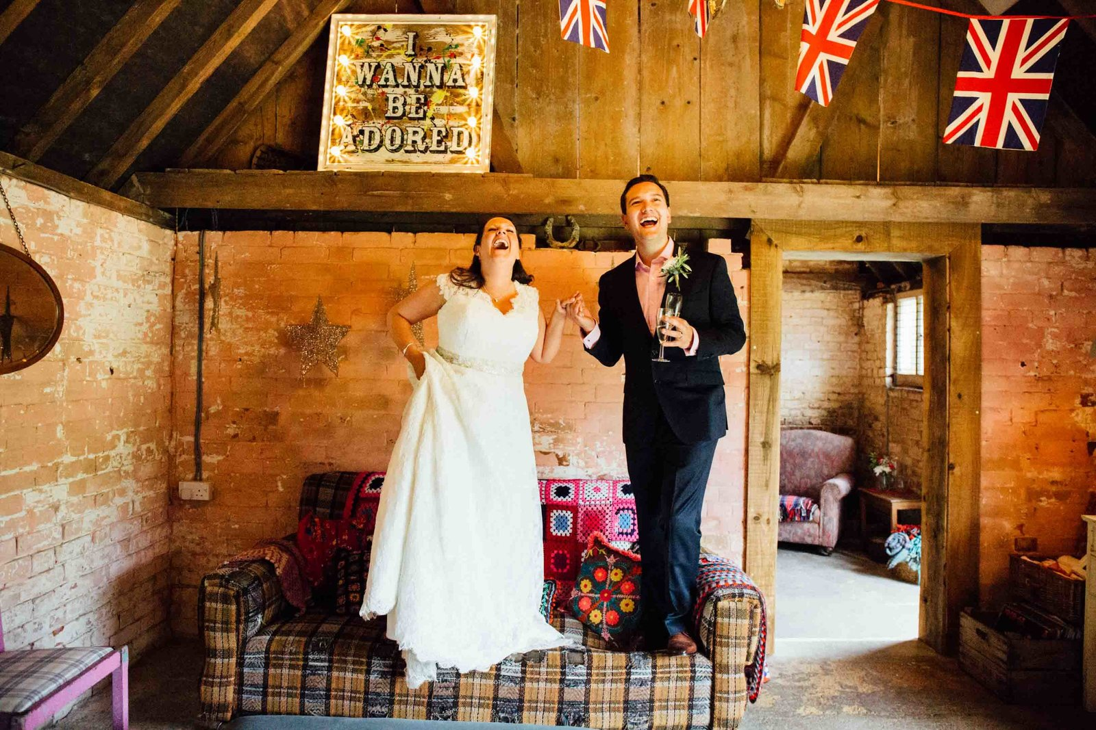 Laughing bride and groom  standing on a chair at The Keeper and The Dell barn wedding in Norfolk